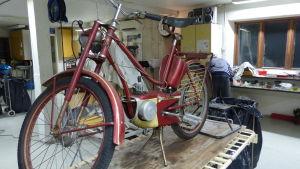 En gammal röd moped på ett bord i en verkstad. Så gammal moped att den mer liknar en cykel