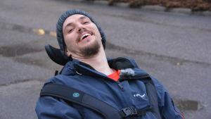 Närbild på Jonas då han lutar sig bakåt i rullstolen och skrattar.