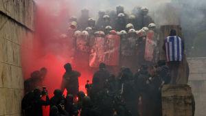 Demonstanter drabbar samman med kravallpolis på Syntagmatorget på söndag eftermiddag.