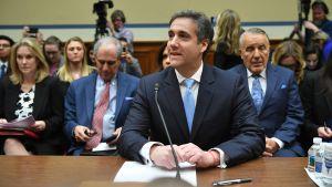 En sällsynt bild av en leende Michael Cohen under utskottsförhöret, med jurister och publik i bakgrunden