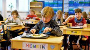 Många elever äter lunch vid sina pulpeter.