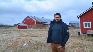 Jesse Mårtensom framför en röd ladugård
