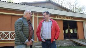 Två män står utanför en danspaviljong och pratar med varandra. Det står Ekenäs FBK på husväggen.