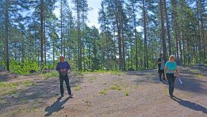 Två kvinnor och en man går omkring på ett område med sand omgivna av en tallskog.