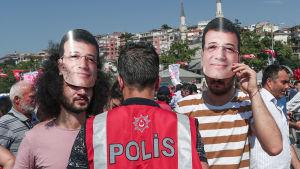Anhängare till Ekrem Imamoglu i masker som föreställer honom under lördagens valmöte.