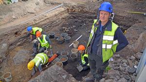 Juuso Koskinen i förgrunden, grävande arkeologer i bakgrunden.