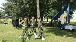 Tre militärklädda män håller en blå fana med bilden av ett vitt Gotlandsfår.