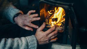 Kädet lämmittelevät kiukaan tulen edessä.