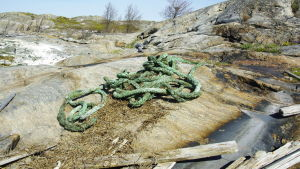 Ett tjockt rep ligger på marken på några klippor. Det ser ut att ha fallit från ett handelsfartyg.