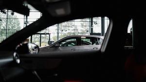 Inuti en bil, utanför står en annan bil.