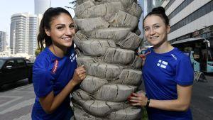 Nooralotta Neziri och Reetta Hurske står vid en palm och ler in i kameran.