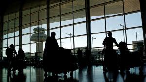 Passagerare i en flygterminal, i bakgrunden lyktstolpar och ett flygledningstorn.