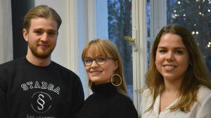 Albert Mattsson, Nelly Karhunen och Emilia Rosenblad står framför ett fönster.