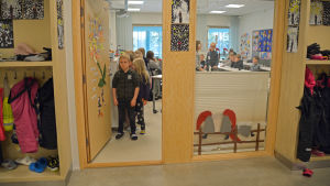 Skolelever står i dörröppningen till ett klassrum.