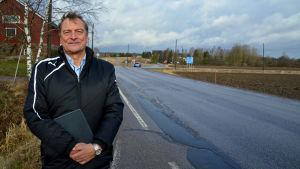 En man står vid sidan av en landsväg.