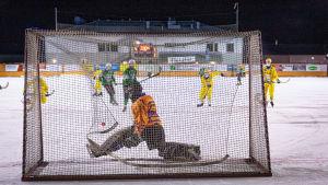 Bilden är tagen bakom ett bandymål. Målvakten försöker hindra motståndarlagets spelare i gröna kläder från att skuta i mål.