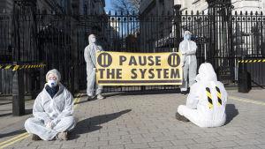 Aktivister i skyddsdräkter och masker kräver hårdare tag mot coronaepidemin i en demosntration Strobritannien.
