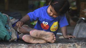 Mamma och barn vid en vägkant i New Delhi 13.4.2020
