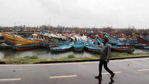 En man promenerar förbi tiotals fiskebåtar