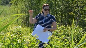 Niina Okkonen står bland gröna träd och grönt gräs. Hon visar med handen hur högt marken ska höjas.