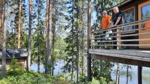 En man och en kvinna står lutade mot ett staket uppe i en trähuskoja i skogen