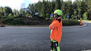 Kvinna i reflexrock och hjälm står och tittar på en rondell som håller på att byggas om.