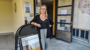 En kvinnor står och lutar mot en skylt utanför en dörröppning till ett hus.