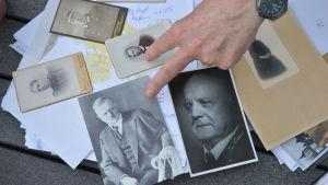 Fotografier på bland andra Jean Sibelius och Henrik Mattsson ligger utspridda på ett bord utomhus.
