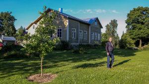 En man står på en gräsmatta framför ett vitt gammalt trähus.