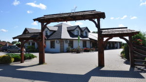 En byggnad i vitt med åstak i mörkt med en portgång i mörkt trä med mörkt åstak. Gården har stenplattor.