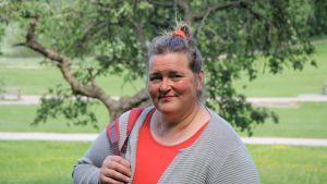 psykologi Liisa-Uusitalo seisoo puistossa takana kaunis puu katsoo lempeästi kameraan
