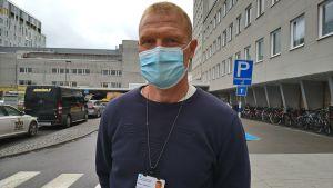 Man med kort ljust hår och munskydd står utanför Vasa centralsjukhus.