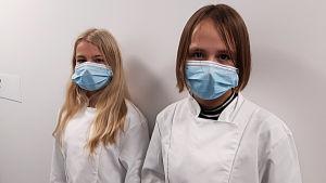 Två flickor i vita skyddsrockar och munskydd.