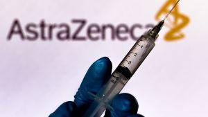 En hand håller i en spruta. I bakgrunden texten AstraZeneca.