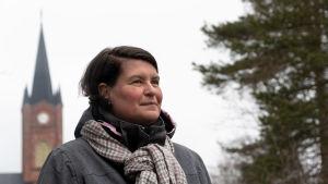 En kvinna iklädd rock och halsduk står utomhus, i bakgrunden Lovisa kyrka.