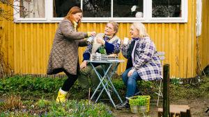 Kädet multaan -ohjelman juontajat Taina Suonio, Enni Koistinen ja Inkeri Alatalo kahvittelevat ulkona.