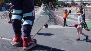 Ung pojke som står med skateboard och skyddsutrustning i Söderviks skatepark