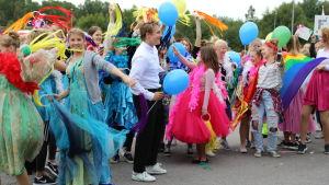 En mängd människor i färggranna kläder står i en klunga med ballonger.