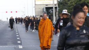 Sörjande i Bangkok, Thailand på väg till kremeringsceremoni.