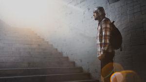 huppupäinen mies seisoo portailla