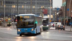 Bussi kaartaa kadulle Rautatientorin bussiterminaalista. Raitiovaunu odottaa takana liikennevaloissa.