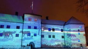 Renar, en björn och Finlands natur projiceras på Åbo slotts fasad i vinternatten i ljusinstallationen Luminous Finland 100.