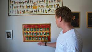 jonas pekar på en affisch över svenska regenters valspråk.