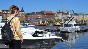 Emmy Nyström står på bryggan vid Skatudden och tittar ner mot vattnet.