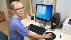 Allmänläkaren Hanna Åsberg sitter framför en dator i ett mottagningsrum på en vårdcentral.