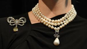 Ett pärlhalsband med en pärlor i flera rader och en droppformad pärla som hänger i det.
