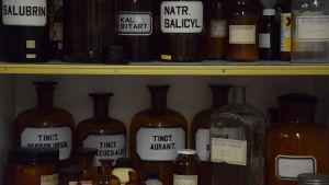 Gamla apoteksflaskor i brunt glas med vita etiketter. Texter på latin.