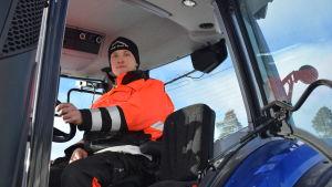 Robin Metsola sitter i traktorn och håller i ratten,