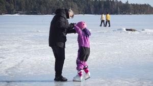 Pappa lär sitt barn att åka skridsko