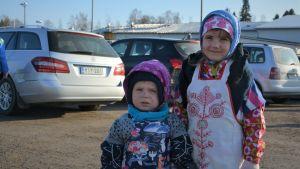 En pojke och en flicka utklädda till påskhäxor.